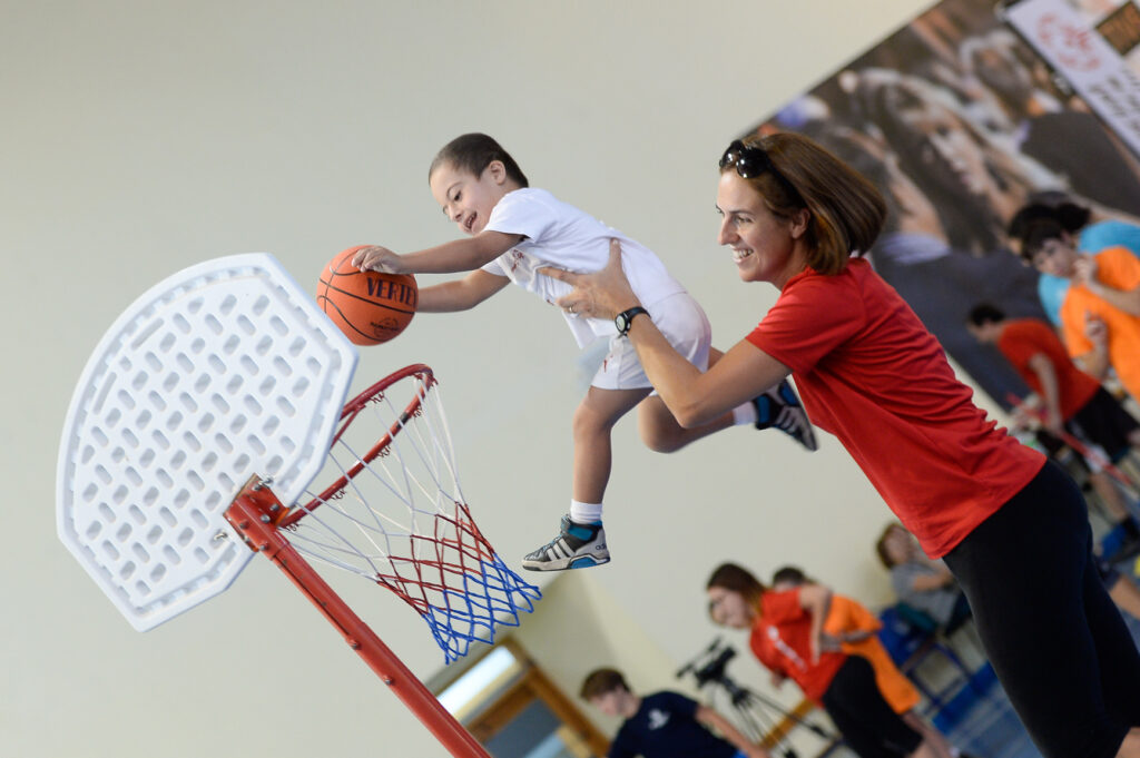 Instructor assisting young boy in basketball